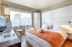 A bed or beds in a room at Mercure Brive