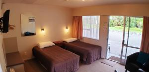 A bed or beds in a room at Glacier View Motel - Franz Josef