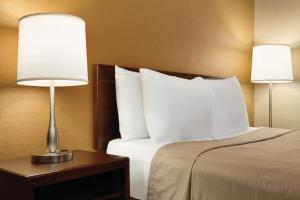 A bed or beds in a room at Travelodge by Wyndham Toronto East
