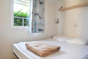 A bed or beds in a room at Camping Les Perouses