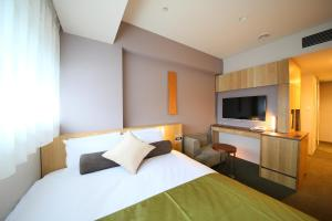 A bed or beds in a room at Hotel Gracery Shinjuku