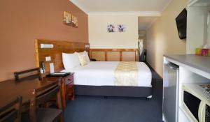 A bed or beds in a room at Highway Motor Inn Taree