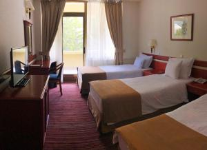 A bed or beds in a room at Hotel Metropol – Metropol Lake Resort