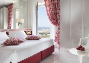 A bed or beds in a room at Hotel Milton Rimini