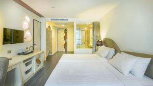 A bed or beds in a room at Le Tada Parkview Hotel