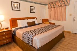 A bed or beds in a room at Riviera Inn