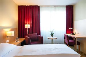 Ein Bett oder Betten in einem Zimmer der Unterkunft Welcome Hotel Paderborn