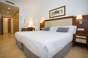 A bed or beds in a room at Aparthotel Albufera