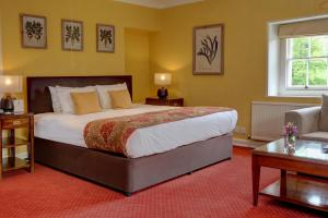 A bed or beds in a room at Best Western Henbury Lodge Hotel