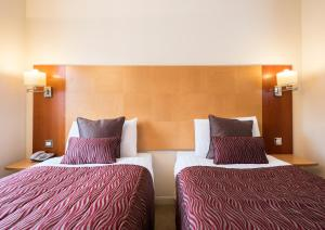A bed or beds in a room at Holyrood Aparthotel