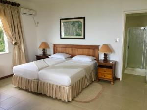 A bed or beds in a room at Beau Séjour Hotel