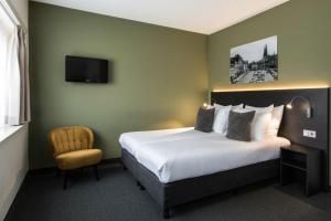 A bed or beds in a room at Hotel Parkzicht Eindhoven