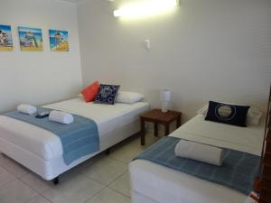 A bed or beds in a room at Shell Motel (Pearly Shell Motel)