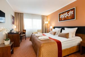 A bed or beds in a room at Avalon Hotel & Conferences