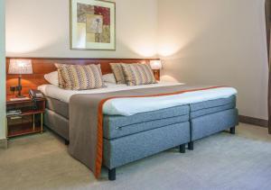 A bed or beds in a room at Golden Tulip Tjaarda Oranjewoud - Heerenveen