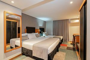 A bed or beds in a room at Slaviero Essential Curitiba Batel