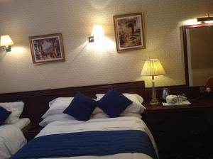 A bed or beds in a room at Avon Hotel