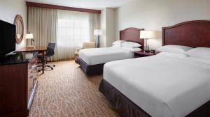 A bed or beds in a room at DoubleTree by Hilton Sunrise - Sawgrass Mills