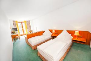 A bed or beds in a room at Hotel Gasthof Raab