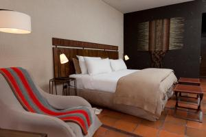 A bed or beds in a room at Nayara Alto Atacama