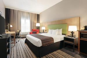 A bed or beds in a room at Country Inn & Suites by Radisson, Nashville Airport East, TN