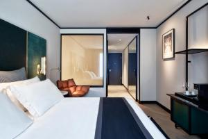 A bed or beds in a room at Academias Hotel, Autograph Collection
