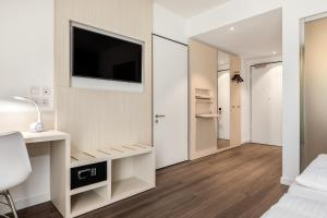 A television and/or entertainment center at Super 8 by Wyndham Oberhausen am Centro