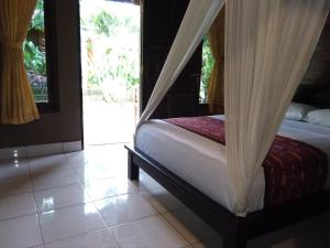 A bed or beds in a room at Suka Sari Cottages