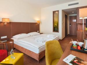 A bed or beds in a room at Austria Trend Hotel Doppio Wien