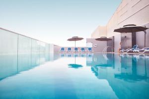 Der Swimmingpool an oder in der Nähe von Treppan Hotel & Suites By Fakhruddin