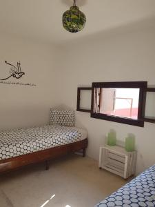 A bed or beds in a room at Riad El Maâti