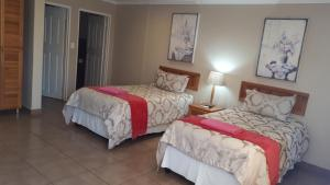 A bed or beds in a room at Rosegarden Guesthouse