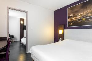 A bed or beds in a room at Brit Hotel Montpellier Parc Expo