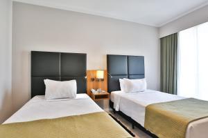 Кровать или кровати в номере Comfort Ibirapuera