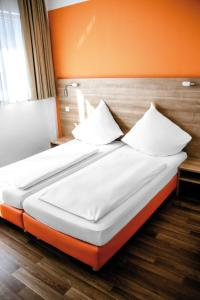 A bed or beds in a room at Orange Hotel und Apartments
