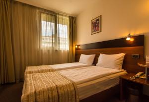 A bed or beds in a room at Hotel Forum - Free Parking