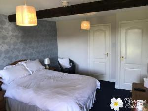 A bed or beds in a room at Primrose Cottage Rooms