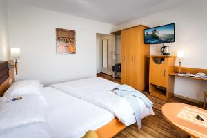 A bed or beds in a room at City Hotel Biel Bienne Free Parking