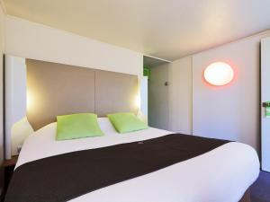 A bed or beds in a room at Campanile Plaisir