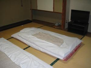 A bed or beds in a room at Matsuichi
