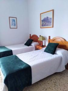 A bed or beds in a room at Pensión Los Volcanes