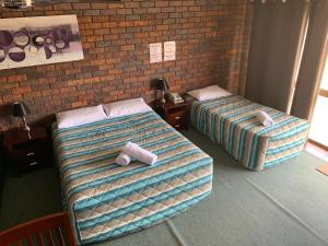 A bed or beds in a room at Bridge Street Motor Inn