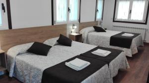 A bed or beds in a room at Albergue y Pensión Boente