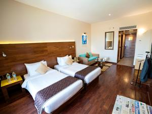 A bed or beds in a room at The Orchid Hotel Hinjewadi Pune