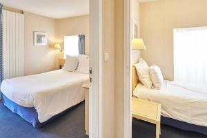 A bed or beds in a room at Hôtel Vacances Bleues Villa Caroline