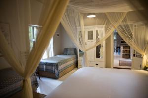 A bed or beds in a room at The Olive Thrush Cottage