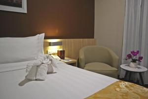 A bed or beds in a room at Horison Sky Kualanamu