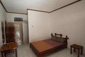 A bed or beds in a room at Bungalow Kempu Taman Ayu I