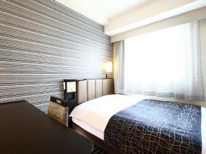 A bed or beds in a room at APA Hotel Higashi Shinjuku Kabukicho