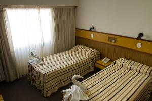 A bed or beds in a room at Costanera Hotel